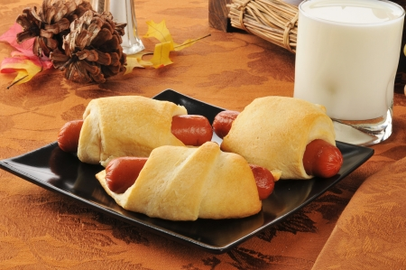 Pigs in a blanket with a glass of milk photo