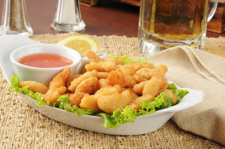 A plate of popcorn shrimp and a mug of beer