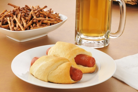 Pigs in a blanket, or glory dogs, with beer and pretzels photo