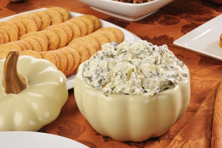 spinach: A crock of spinach artichoke parmesan dip with wheat crackers Stock Photo