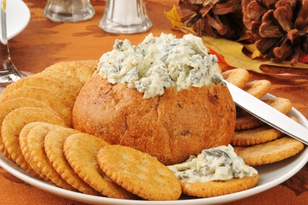 Spinach artichoke parmesan dip in a bread bowl with wheat crackers