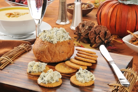 Spinach artichoke parmesan dip in a bread bowl with pretzels and butternut squash soup