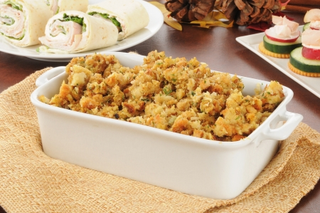 A baking dish with turkey stuffing and holiday appetizers Stock Photo