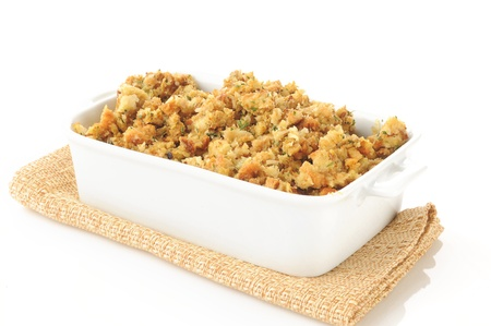 A casserole dish of herb stuffing in turkey broth on a white background 스톡 콘텐츠