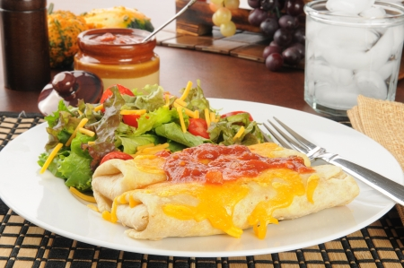 chimichangas topped iwth melted cheddar cheese and salsa with a salad