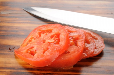 Sliced tomatoes on a cutting board with a knife