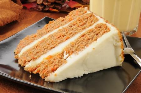 egg nog: A slice of gourmet carrot cake and a glass of pumpkin spice egg nog