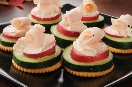 Party tray of cucumber, raddish, cream cheese and ham canapes
