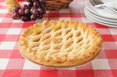 A peach pie with a lattice crust on a picnic table Stock Photo