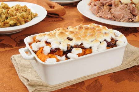Sweet potato casserole topped with cranberries, candied walnuts and marshmallows photo