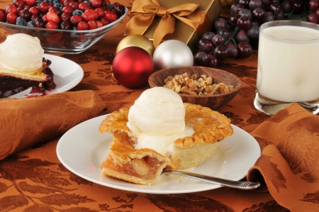 An individual sized apple pie on a table with Christmas decorations photo