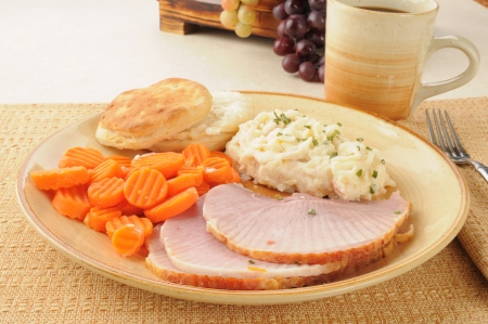A ham dinner with carrots, biscuits and mashed potatoes