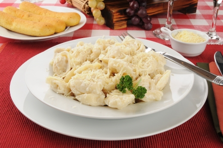 alfredo: A bowl of cheese tortellini with garlic bread sticks Stock Photo