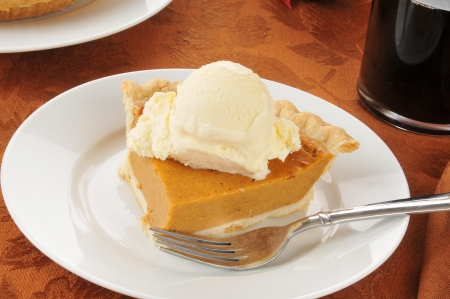 A slice of pumpkin pie with vanilla ice cream and hot spice wine photo