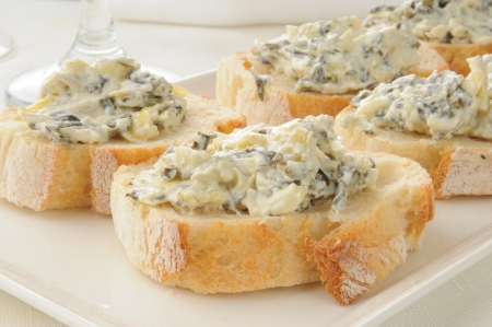 Closeup of spinach artichoke dip on Italian toast
