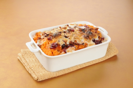A dish of sweet potato casserole on a hot pad photo