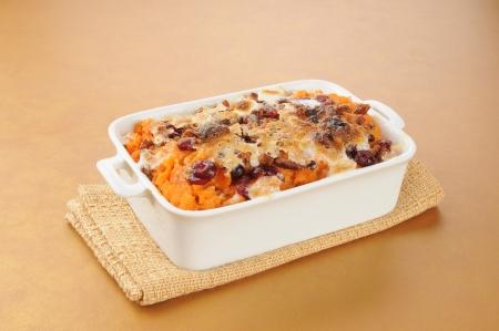 A dish of sweet potato casserole on a hot pad Standard-Bild