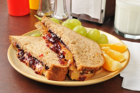 jam sandwich: A peanut butter and jelly sandwich with oranges and grapes