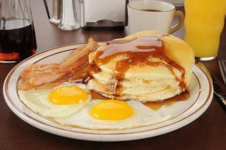 in syrup: Un desayuno de tocino y huevos con tortitas y zumo de naranja