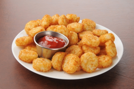 catsup: A plate of hash browns potato cakes with catsup