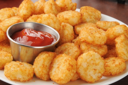 catsup: Closeup of hash brown potato cakes with catsup