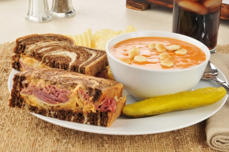 A reuben sandwich on marbled rye with tomato bisque soup