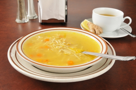cold remedy: A bowl of hot chicken noodle soup with green tea, lemon and ginger, a natural cold remedy Stock Photo