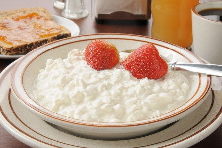 A bowl of cottage cheese and strawberries with apple juice and toast