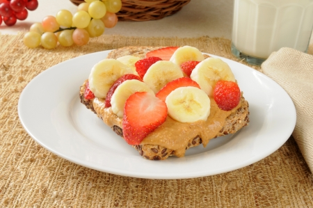 Sprouted seed bread topped with organic peanut butter, bananas and strawberries