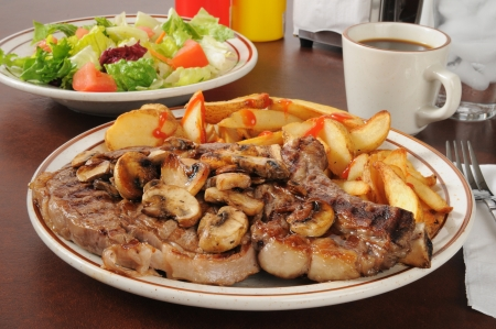 A juicy rib steak with potato wedges and a garden salad Stock Photo - 17992839