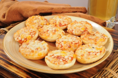 A snack plate of pizza bagels with a mug of beer in the background