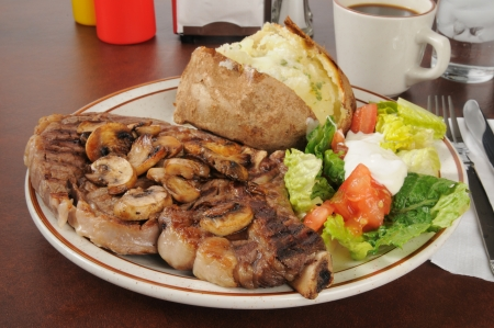A grilled rib steak with baked potato and salad Stock Photo - 18022709