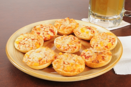 A plate of bagels with pizza toppings and a mug of beer on a bar counter Stock Photo