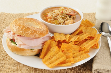 A ham sandwich on a bagel with chicken sausage gumbo and natural chips photo