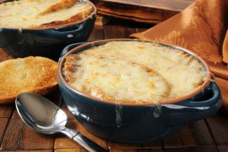 gruyere: A bowl of French onion soup topped with Italian toast and Gruyere cheese