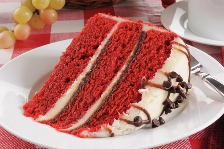 A slice of red velvet cake with chocolate chip icing