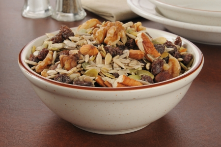 sunflower seeds: A bowl of healthy trail mix with raisins, pecans, walnuts, almonds and sunflower seeds Stock Photo