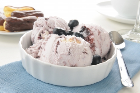 A bowl of blueberry cheeseckae ice cream with mini chocolate eclairs photo