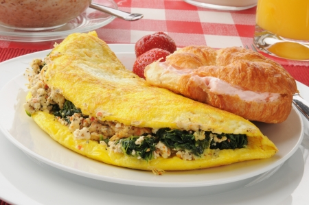 A spinach and feta cheese omelet with a croissant photo