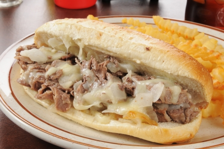 A Philadelphia cheese steak sandwich with french fries