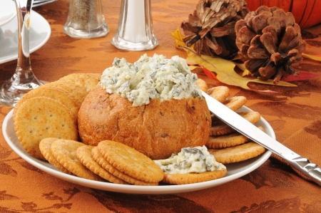 Spinach artichoke parmesan dip in a bread bowl with crackers