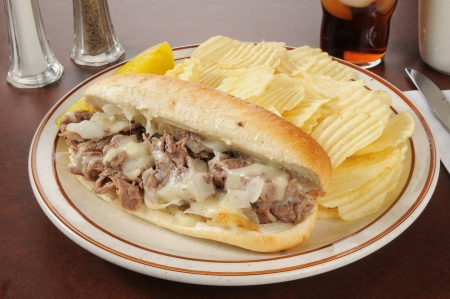 A Philly cheese steak sandwich with french fries and cola