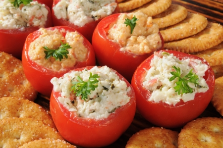 A party setting with tomatoes stuffed with crab and spinach dip and crackers
