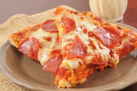 パルメザン チーズを皿にペパロニのピザのスライス 写真素材