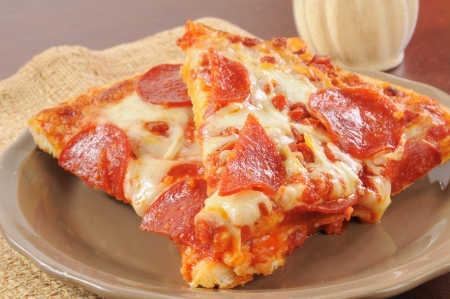 plate: slices of pepperoni pizza on a plate with parmesan cheese