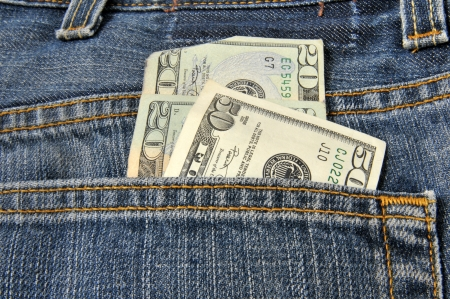 Money coming out of the back pocket of a pair of blue jeans photo