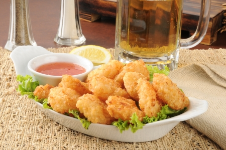 Coconut shrimp with sweet and sour sauce and a mug of beer Archivio Fotografico
