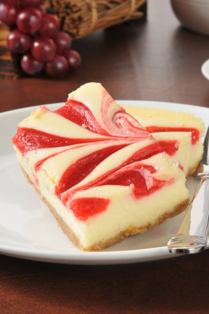 A plate of cheesecake with raspberry or strawberry swirls Reklamní fotografie
