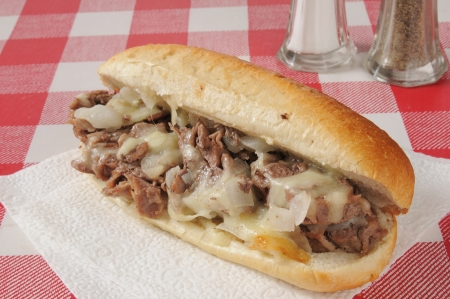 A Philly cheese steak sandwich on a picnic table