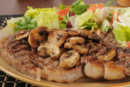 A thick juicy rib steak topped with sauteed mushrooms and served with a garden salad Stock Photo - 19935126